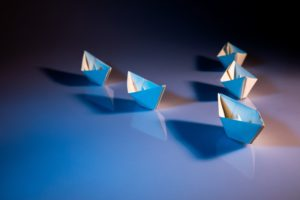 Group of paper boats with one leading