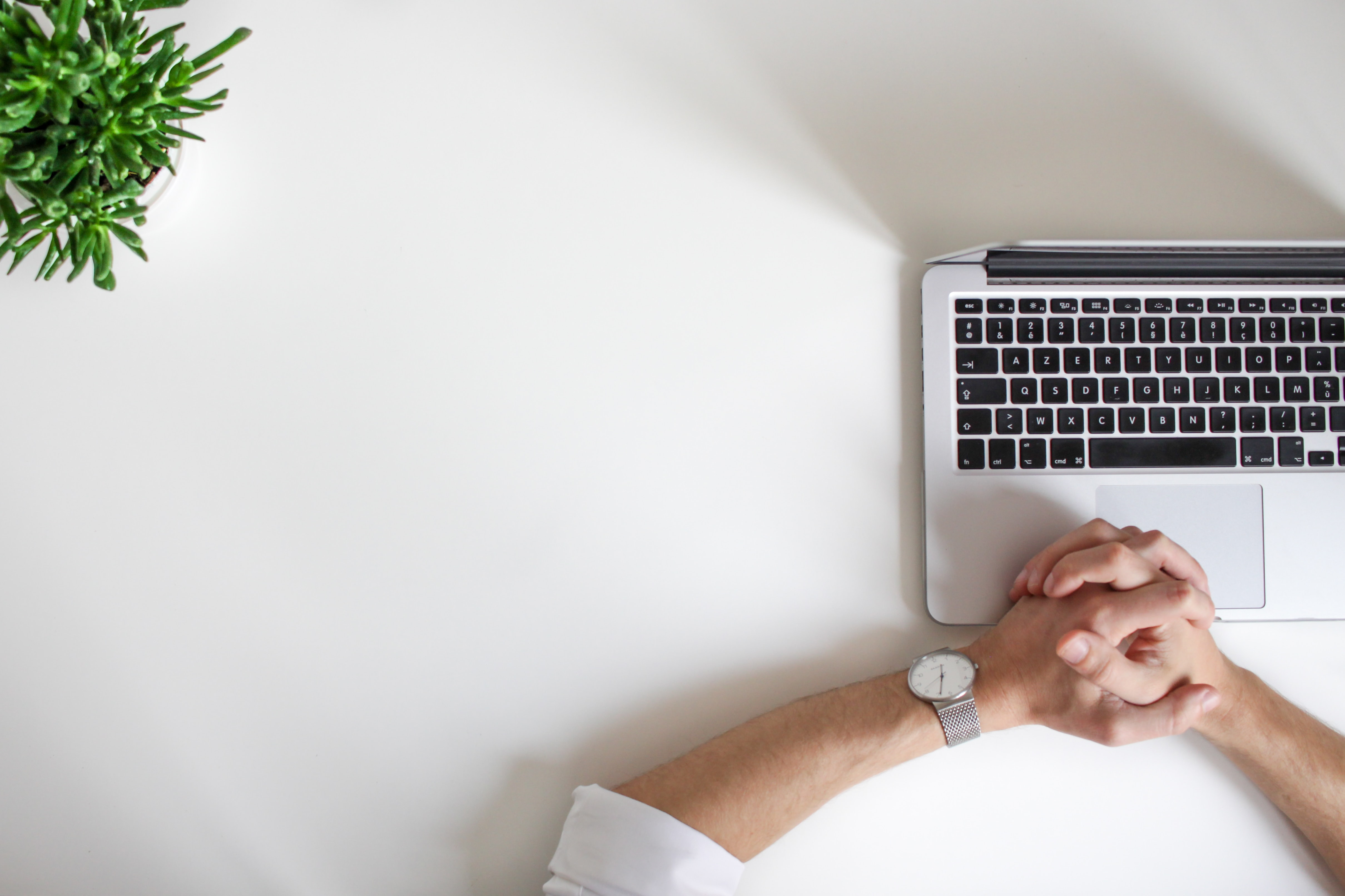 Person with clasped hands in front of laptop, possibly working remotely from home